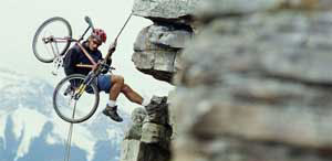 Photo of a mountain climber carrying a bike