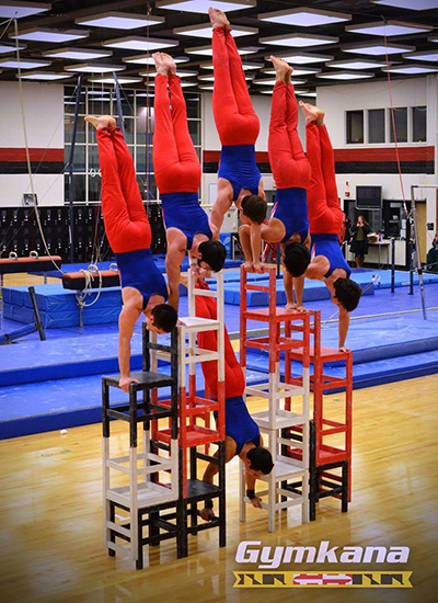 A group of gymkana athletes balancing on chairs doing handstands
