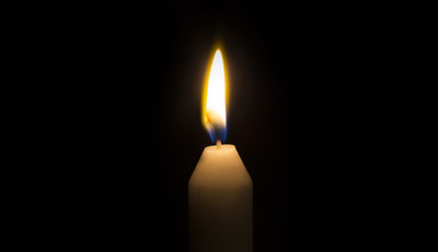 A single candle burning in the dark