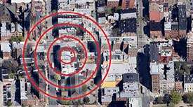 An arial view of a city targeted on one specific location with red bulls eye circles.