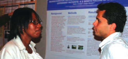 photo of two researchers in front of a scientific poster presentation