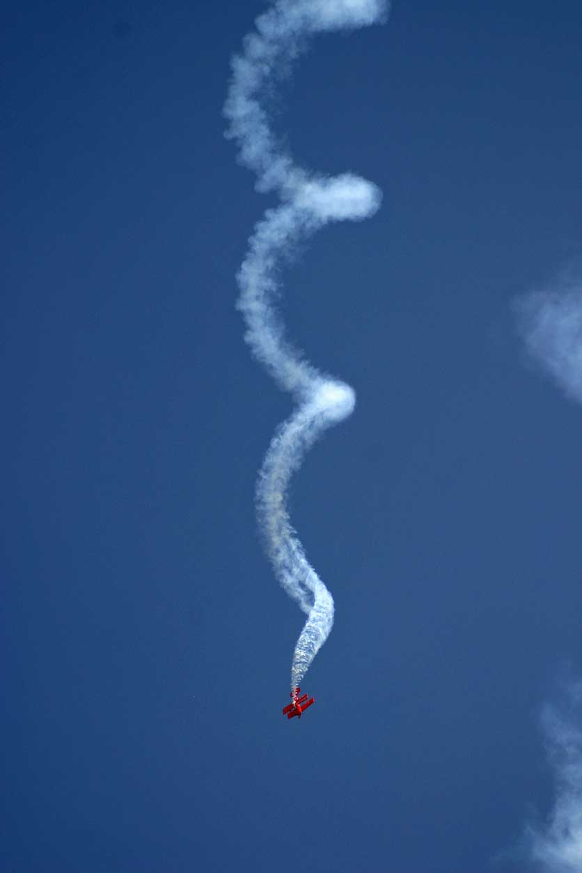 Photo of a plane spiraling down with smoke behind it.