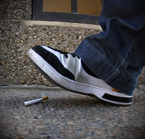 Foot getting ready to stomp out a cigarette