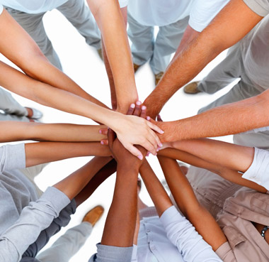 A group of people with their hands in the middle of a circle