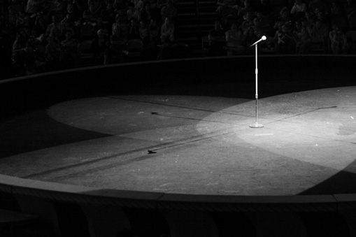 A microphone alone in the middle of an empty stage