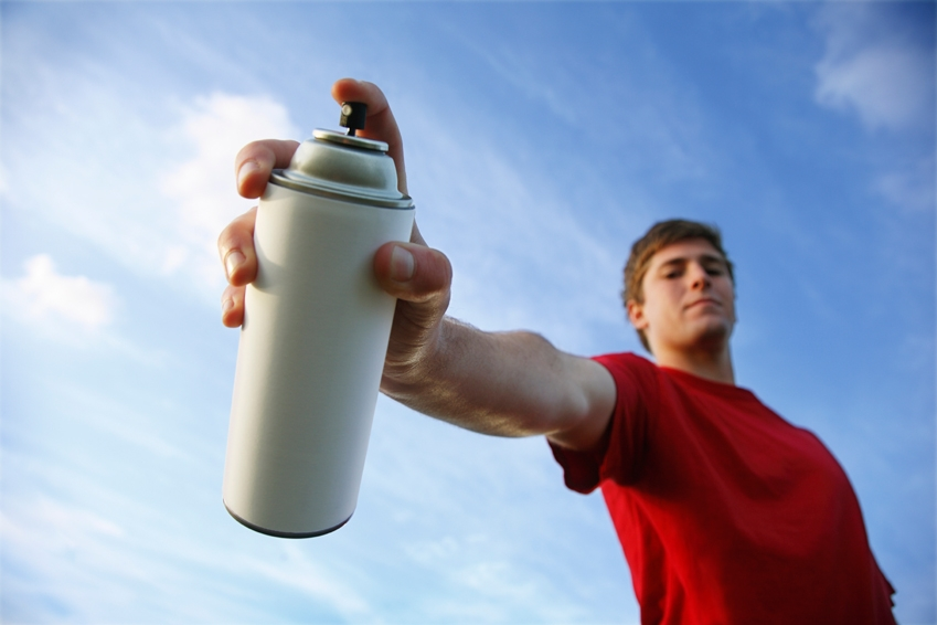 Photo of a young man holding an aerosol can