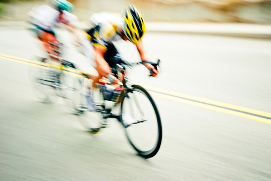 Bicyclist blurred to show speed