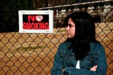 Girl standing next to No Smoking sign