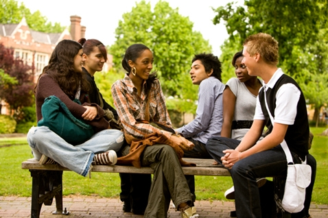 A diverse group of teens sitting on and around a picnic table