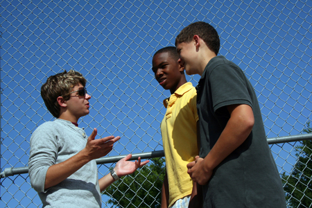 A group of teens talking in front of a fence