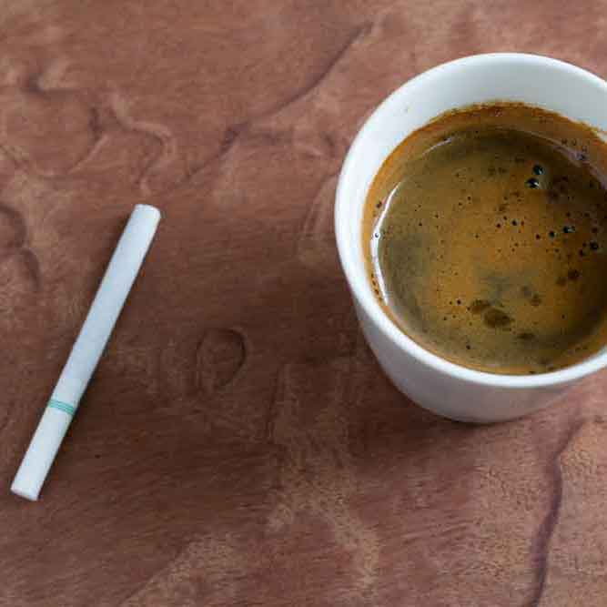 Image of a cigarette next to a cup of coffee