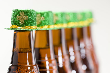 A row of beer bottles with Shamrock hats
