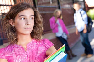 Photo shows a teenage girl walking alone in a schoolyard and glancing over her shoulder at a pair of teens behind her.