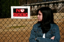 Teen girl leaning against a metal fence that has a sign stating No Smoking