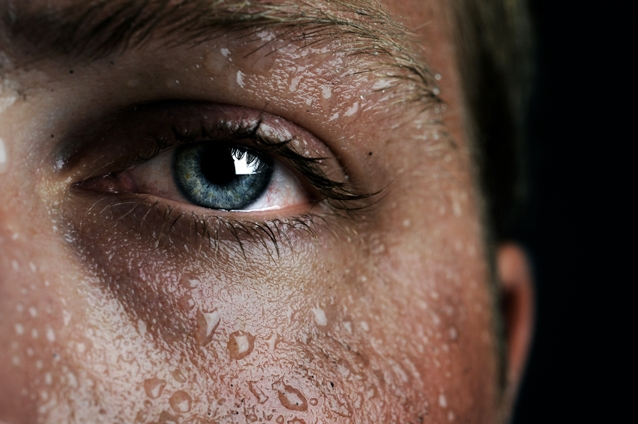 A close up of a face covered in sweat